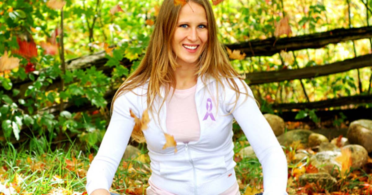 Woman wearing lupus awareness ribbon sitting outside with leaves falling