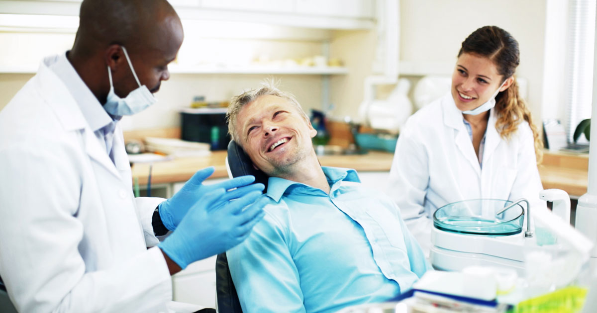 A dentist, dental assistant and patient are talking