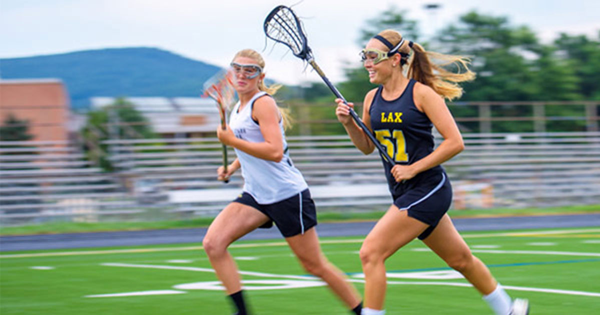 Two women running and playing lacrosse