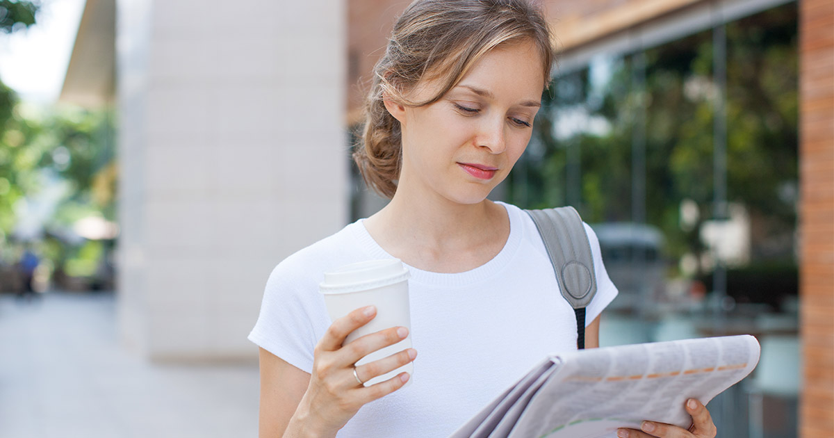 Woman holding coffee and reading newspaper