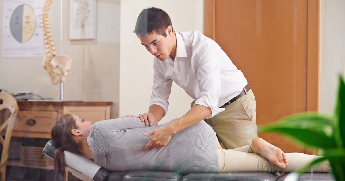 Person lying on examination table with chiropractor twisting leg across their body