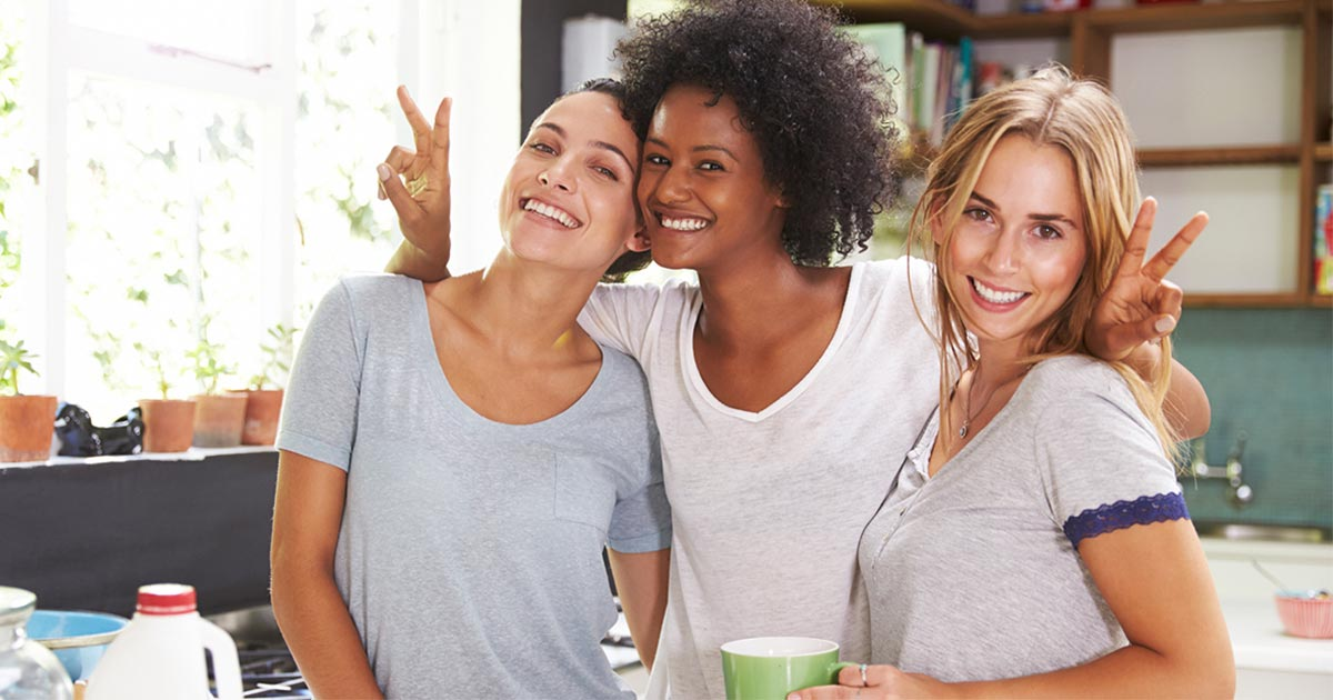 Three woman standing in a kitchen holding coffee mugs and smiling