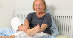 Woman sitting on bed, holding foot