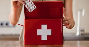 Woman taking pills out of a first aid box