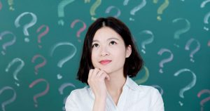 Woman in front of blackboard with question marks on it