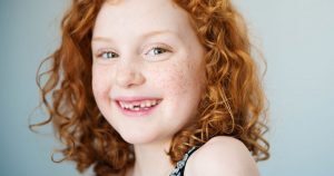 Red haired girl with a few teeth missing