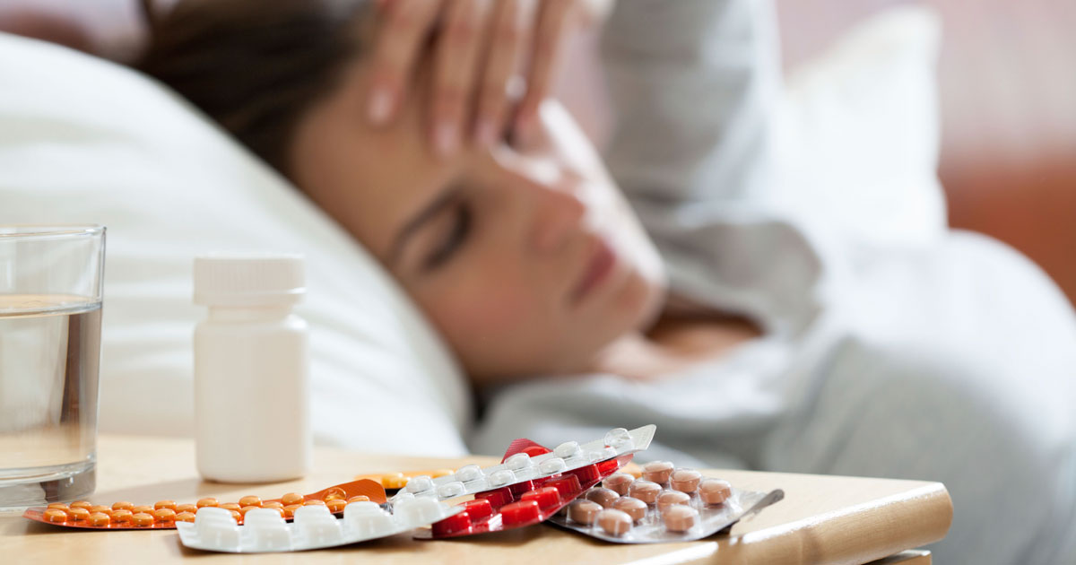 Woman is in bed sick with cold and flu medicine by her bedside table