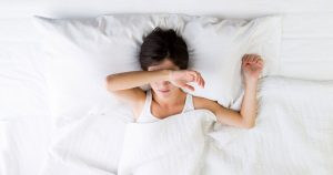 A woman is laying in bed due to fatigue
