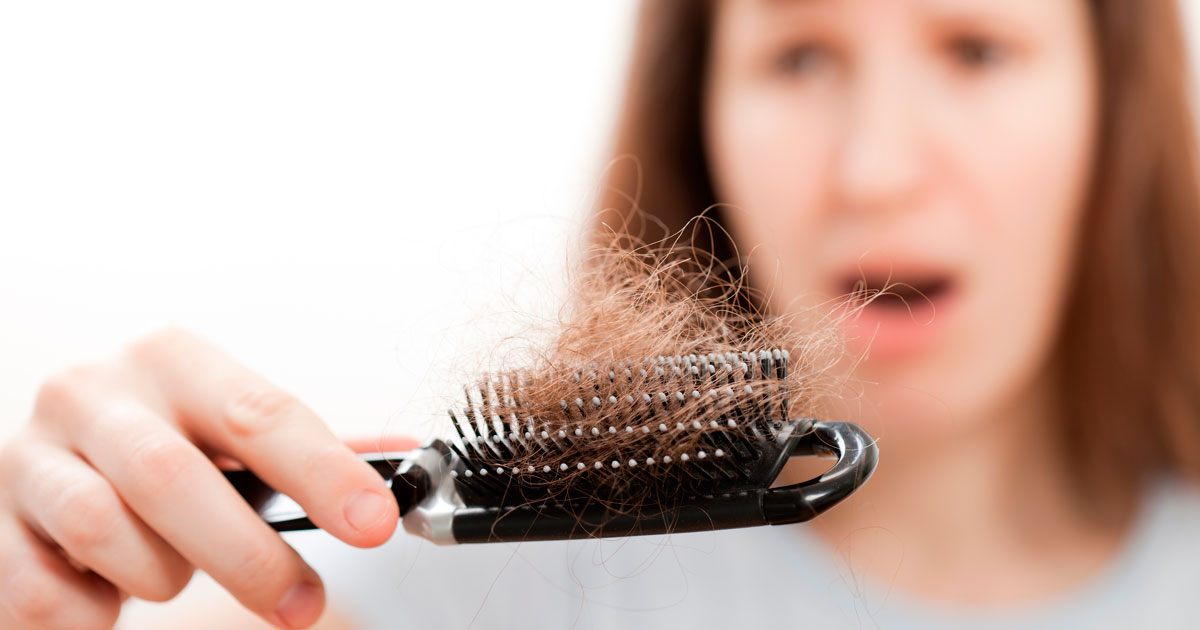 Woman experiencing hair loss with hairbrush