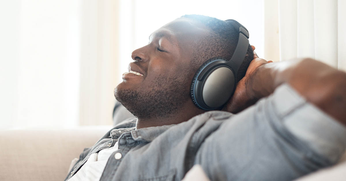 Young man relaxing at home with his headphones on