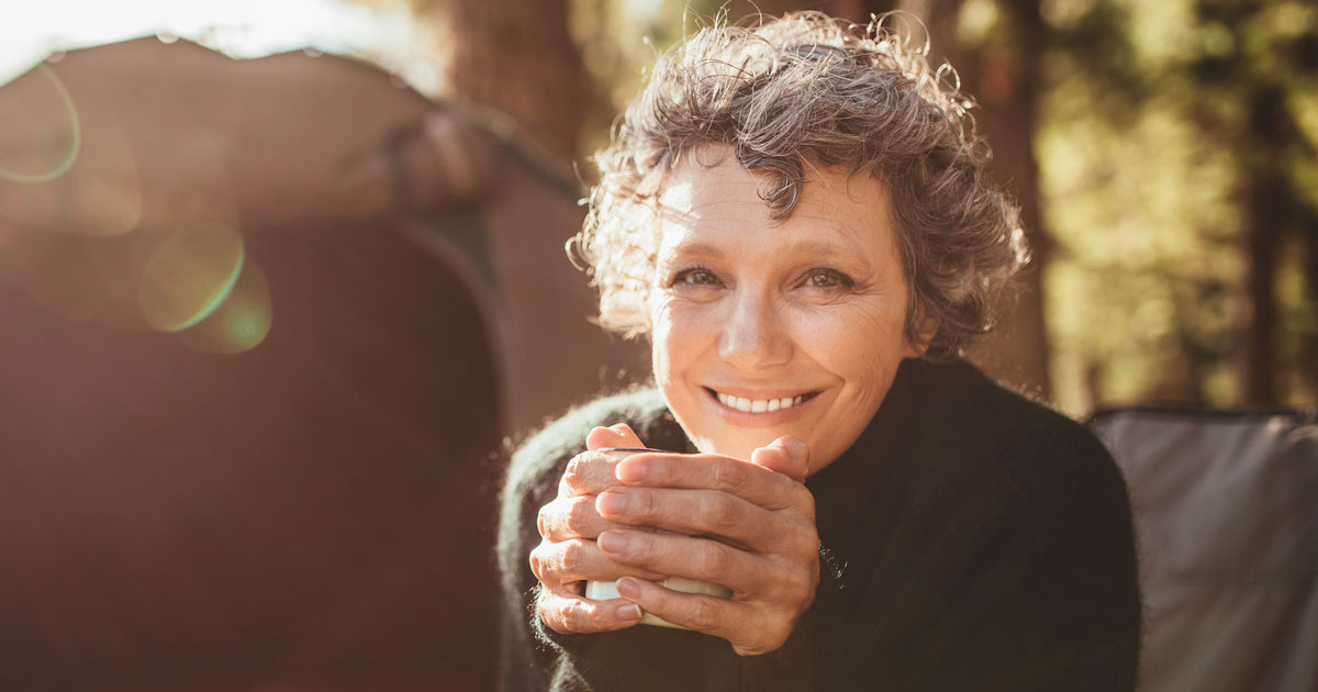An older woman is smiling with a cup of coffee