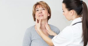 A doctor is physically examining a patient's thyroid