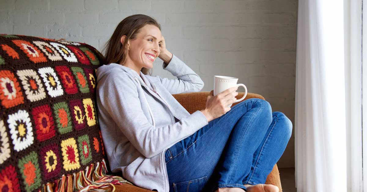 Woman is sitting on a coach with a cup of coffee in hand while smiling