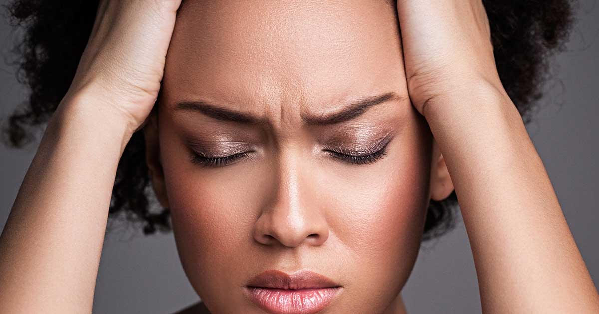 A woman is experiencing a headache or head pain