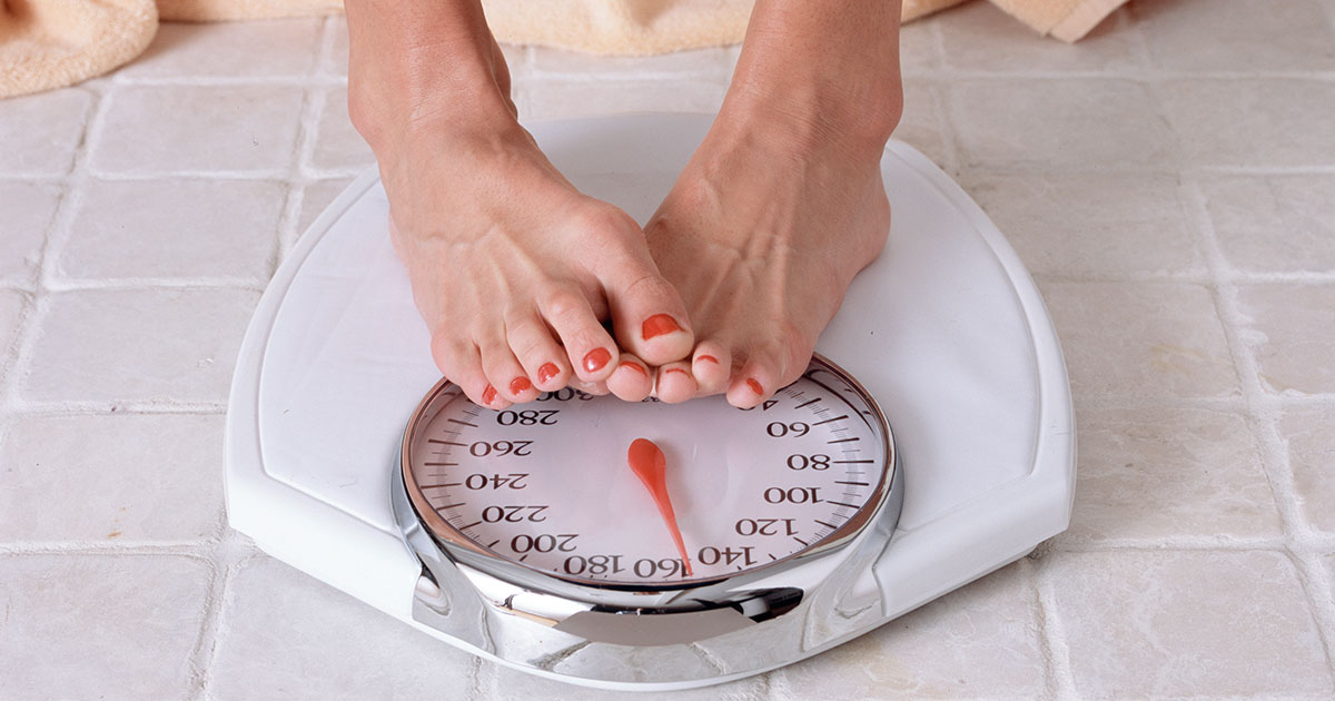 A person is standing on a weight scale