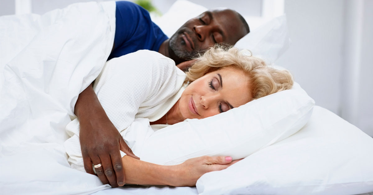 A couple sleeping together in bed