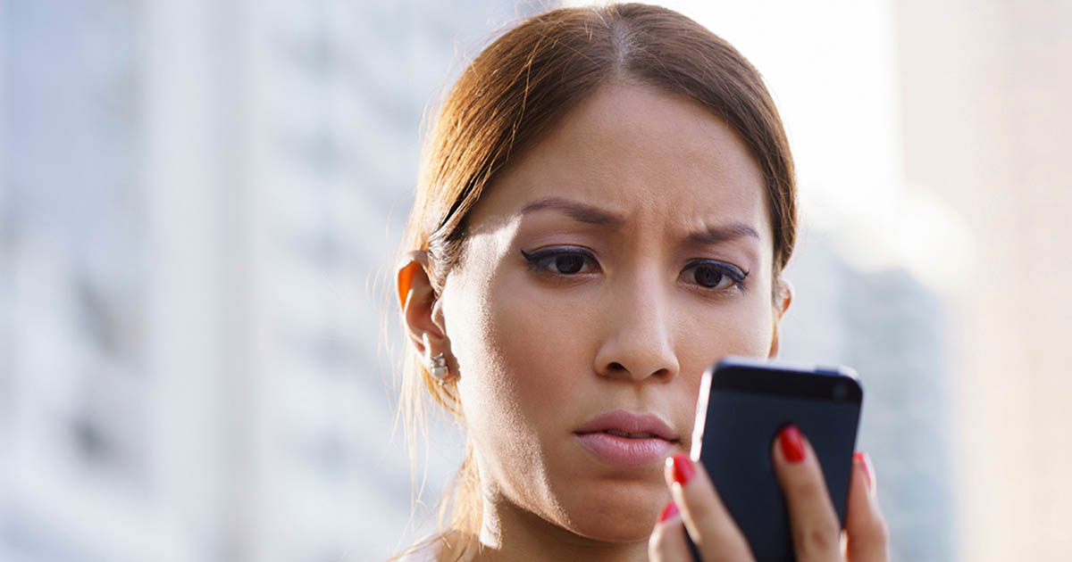 A woman is looking at her phone with a concerned look