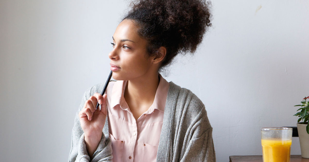 A woman is thinking with a pen by her mouth