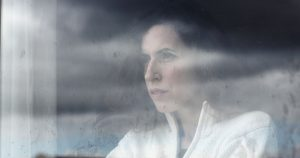 A woman is looking through a foggy window with a sad expression