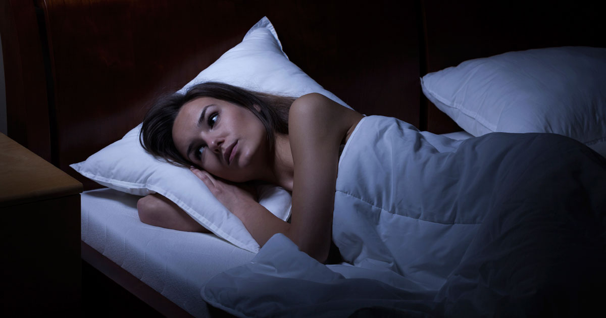 A woman is laying awake in bed late at night