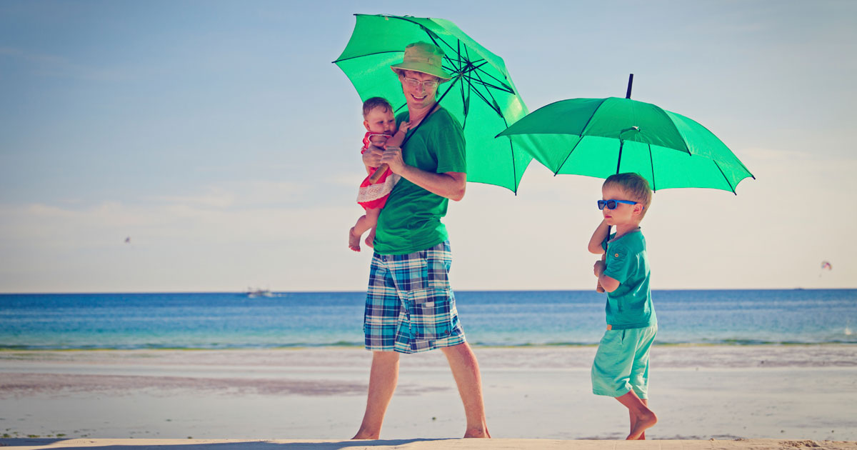 Family walking on the beach with an umbrella