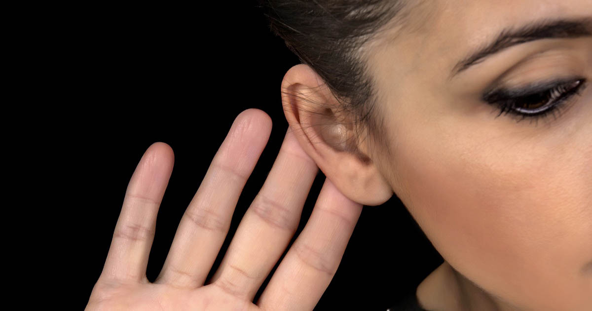 A woman's hand is up close to her ear