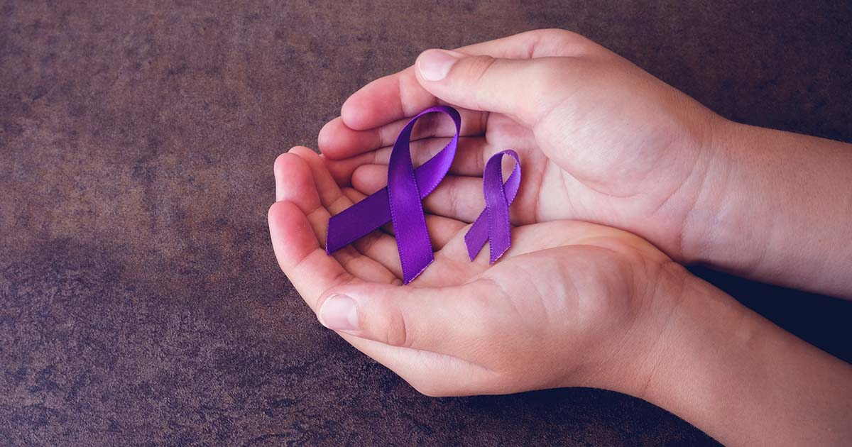Hands holding two purple ribbons