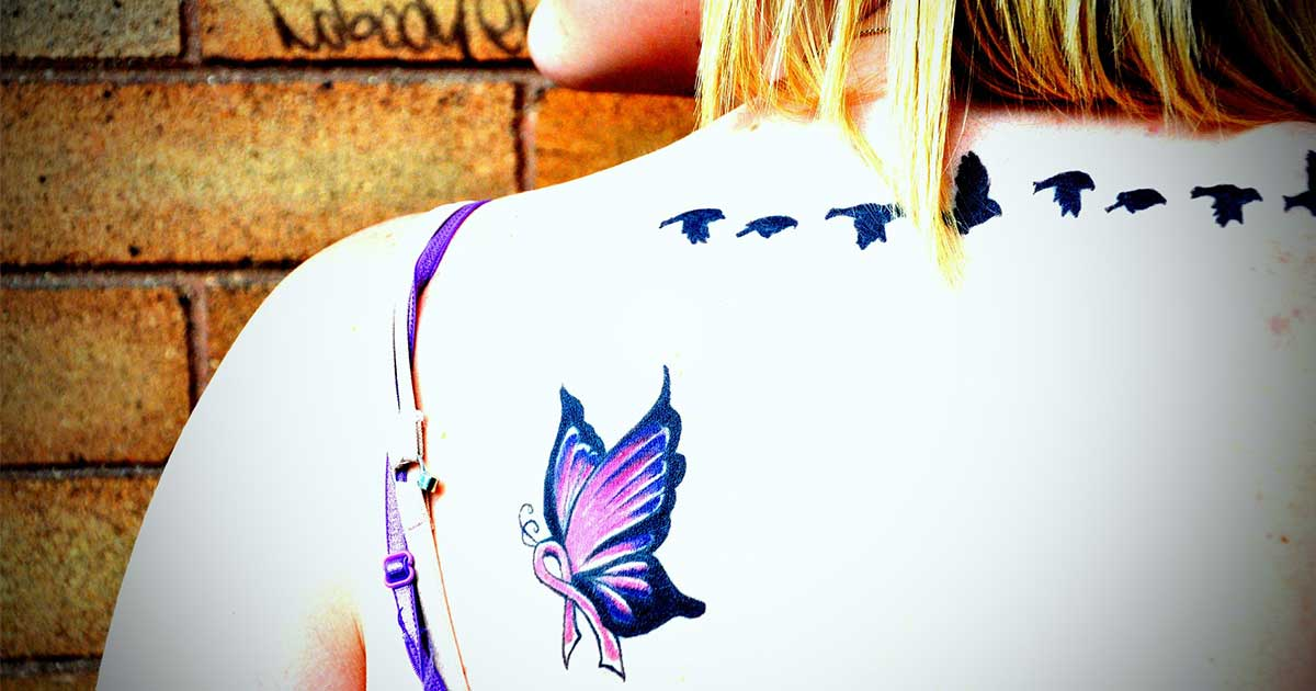 a purple butterfly and ribbon, an example of a lupus tattoo